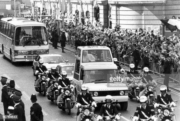 Police motorcyclists provide an escort for John Paul II in his �popemobile� a specially adapted Range Rover on the papal procession from Victoria to...