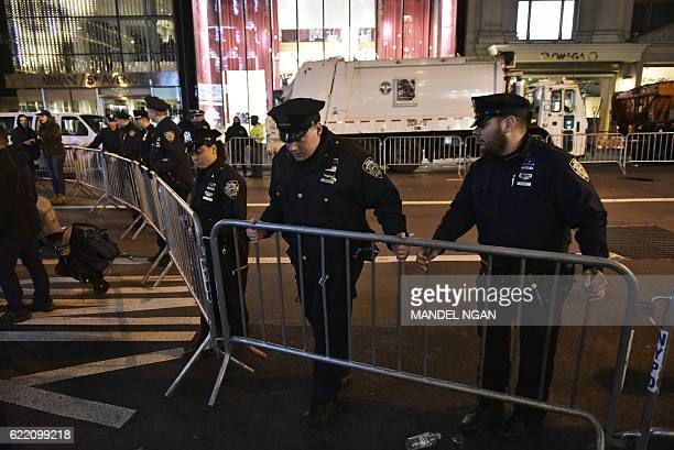 Police move a barricade on 5th Avenue near Trump Tower on November 9 2016 in New York after Donald Trump was elected as the next president of the US...