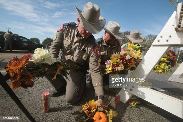 Police move flowers placed at a barricade near the First Baptist Church of Sutherland Springs on November 6 2017 in Sutherland Springs Texas...