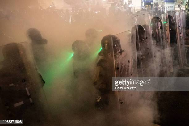 Police move forward through tear gas as they clash with protesters after an antiextradition bill march on July 21 2019 in Hong Kong China...