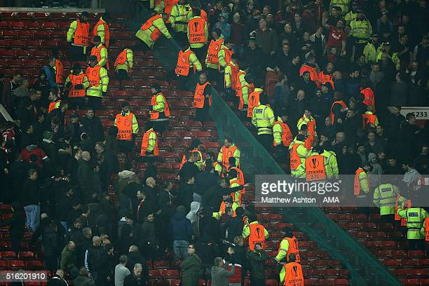 Police move in as rival supporters clash during the UEFA Europa League Round of 16 Second Leg match between Manchester United and Liverpool at Old...
