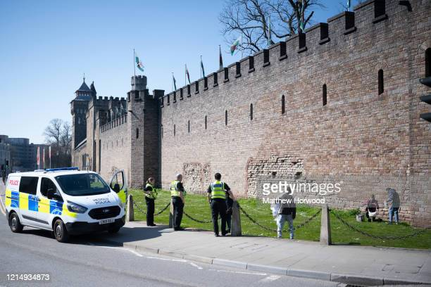 Police move on a group of three people from Cardiff Castle on March 26 in Cardiff Wales The Coronavirus pandemic has spread to many countries across...
