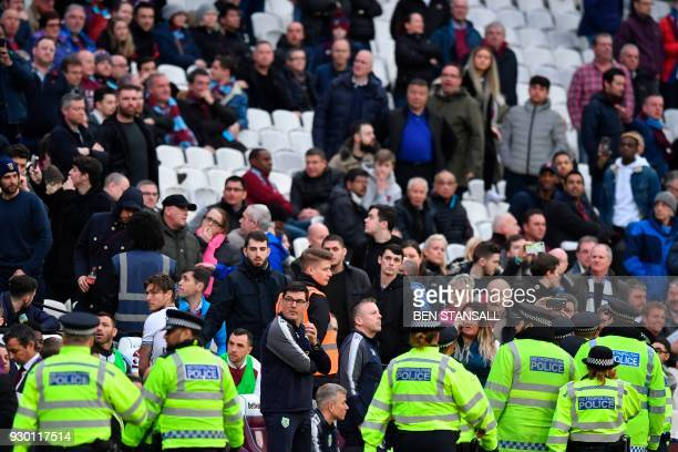 Police move onto the pitchside during the English Premier League football match between West Ham United and Burnley at The London Stadium in east...