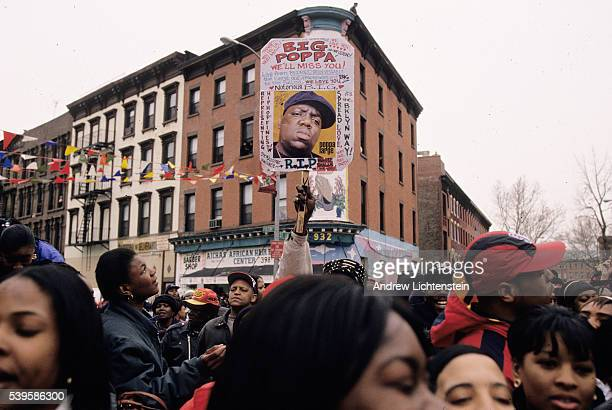 Police neighbors and fans wait and watch as the funeral caravan for rap artist Christopher Wallace known as Notorious BIG passes through the Brooklyn...