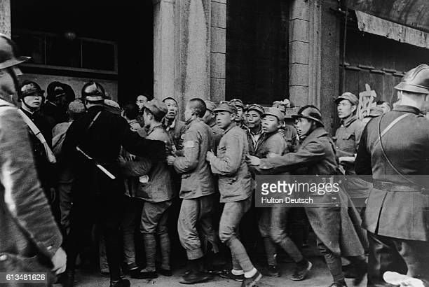 Police of the French Concession zone near Shanghai administer a group of refugees who have fled from the Japanese capture of neighboring Nantao...