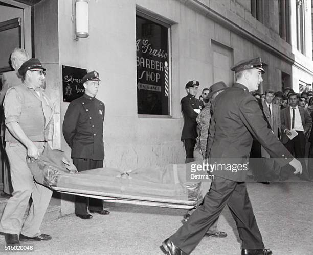 Police of the morgue detail carry the body of Albert Anastasia onetime Lord High Executioner of Murder Inc past the barber shop sign at the Park...
