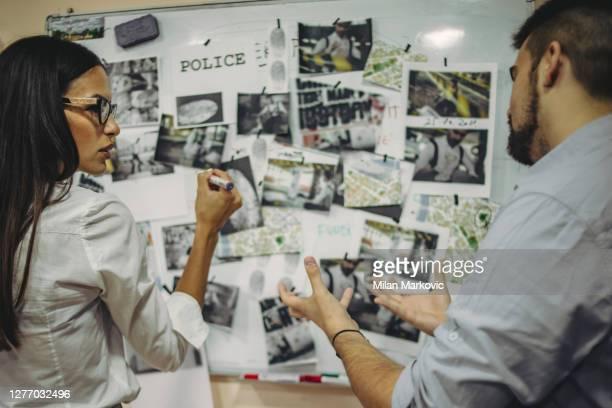 犯罪捜査に協力する警察署の同僚 - 男女、刑事、fbi捜査官が在任中の事件で協力 - 警察署長 ストックフォトと画像