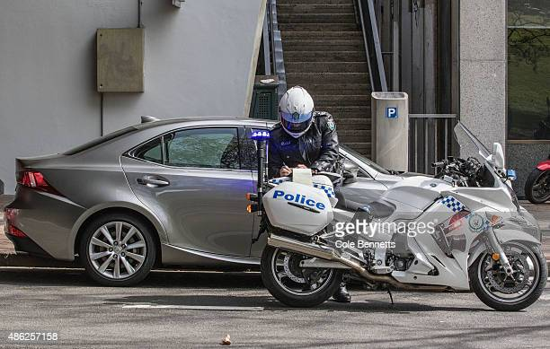 A police office on a motorbike books a car that is parked on the road designated for the parade path on September 3 2015 in Sydney Australia The...