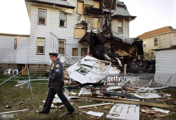 Police office walks past a house damaged by a falling engine from the crash of American Airlines Flight 587 November 13, 2001 in the Rockaway section...