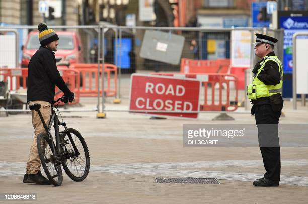 A police officer adheres to social distancing measures as he talks with a cyclist in Leeds northern England on March 30 as life in Britain continues...