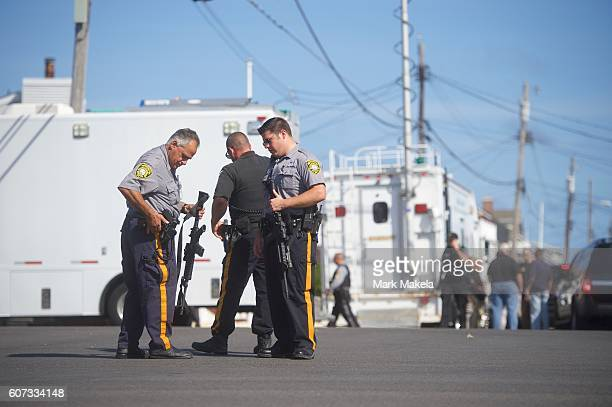 A police officer adjusts his firearm near the scene of an 'pipe bombstyle device' explosion on September 17 2016 in Seaside Park New Jersey The...