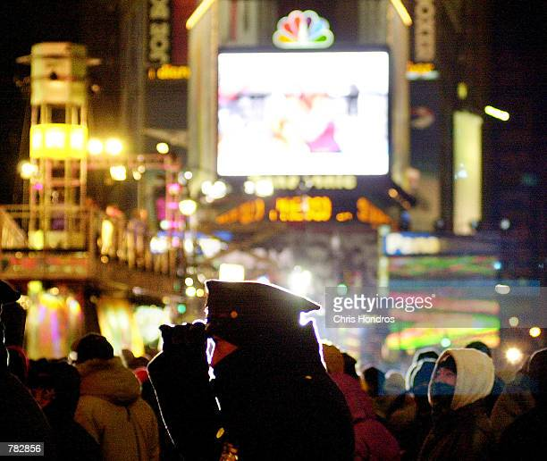 A police officer adjusts his hat December 31 2000 while waiting for the ball to drop in Times Square in New York Undaunted by cold temperatures and a...