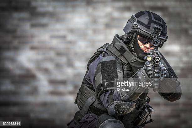 swat police officer against brick wall - 銃 ストックフォトと画像