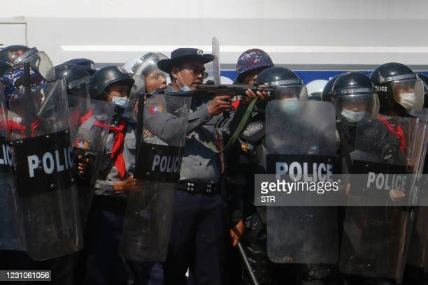 Police officer aims a gun during clashes with protesters taking part in a demonstration against the military coup in Naypyidaw on February 9, 2021.