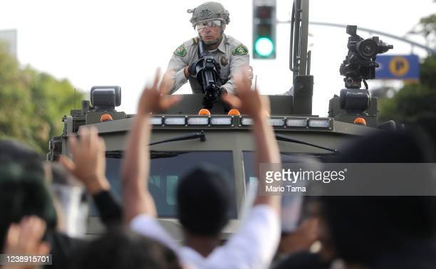 A police officer aims a nonlethal weapon as protesters raise their hands during demonstrations in the aftermath of George Floyd's death on May 31...