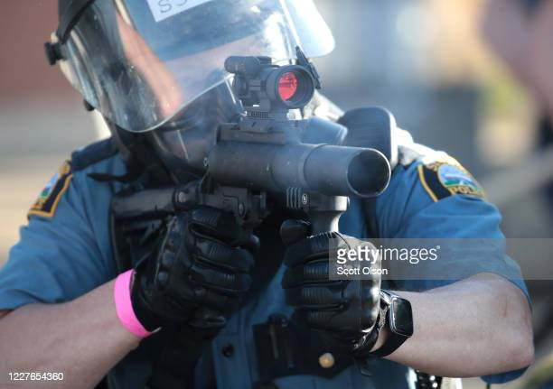A police officer aims a tear gas gun at protesters on May 28 2020 in St Paul Minnesota Today marks the third day of ongoing protests after the police...