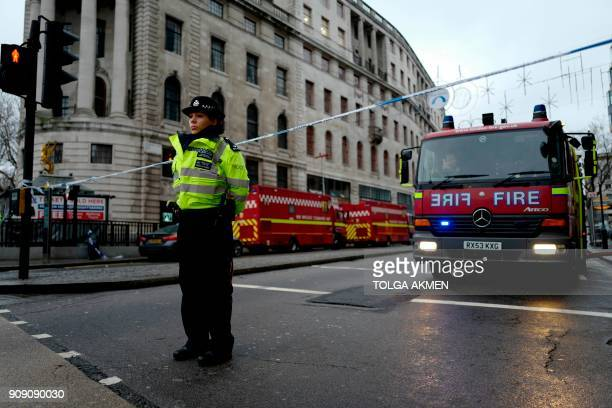 A police officer and a fire engine are seen at a police cordon enar Charing Cross railway station in London on January 23 2018 following a gas leak...