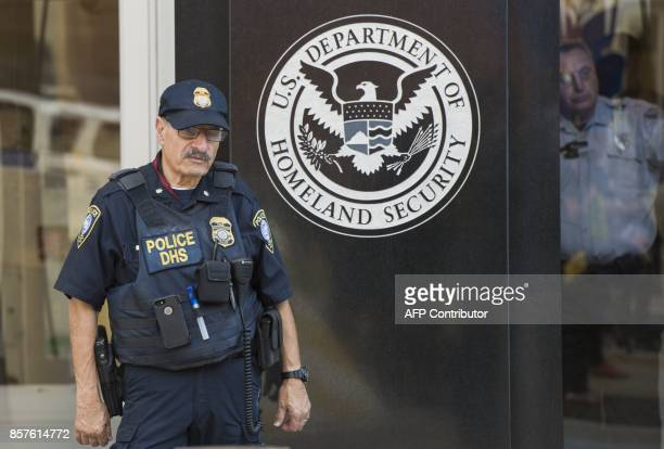 A police officer and a security officer look on at the US Immigration and Customs Enforcement office part of the Department of Homeland Security in...