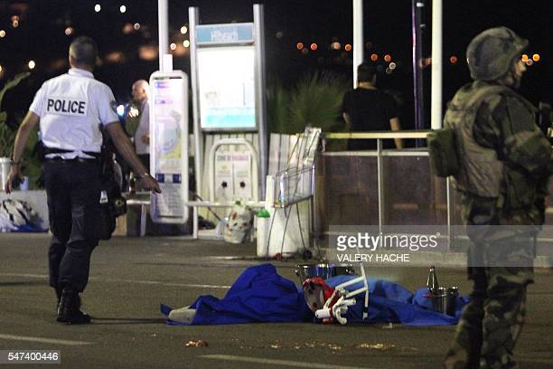 A police officer and a soldier stand next to a dead body covered with a blue sheet on the Promenade des Anglais seafront in the French Riviera town...