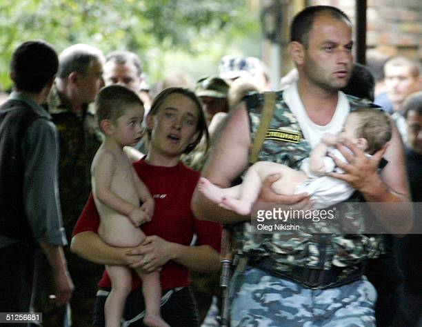A police officer and a woman carry two recently released children near a school taken over by terrorist on September 2 2004 in the town of Beslan...