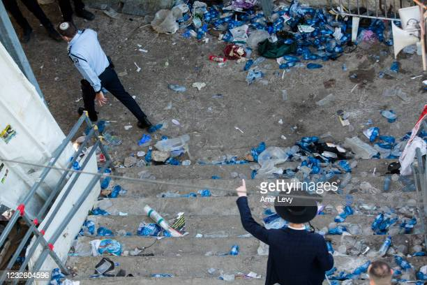 Police officer and an Ultra Orthodox Jewish man walk at the scene where dozens were killed in crush at a religious festival in Mount Meron on April...