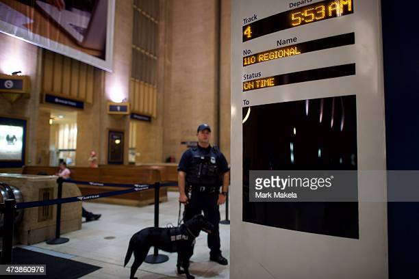 A police officer and dog stand beside a notice board at 30th Street Station listing the 553am first train as Amtrak resumes northbound service after...