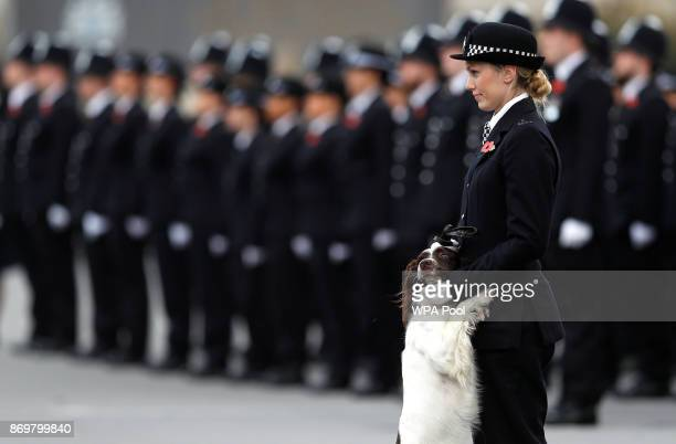 A police officer and her police dog stand to attention as they attend the Metropolitan Police Service Passing Out Parade in Hendon on November 3 2017...