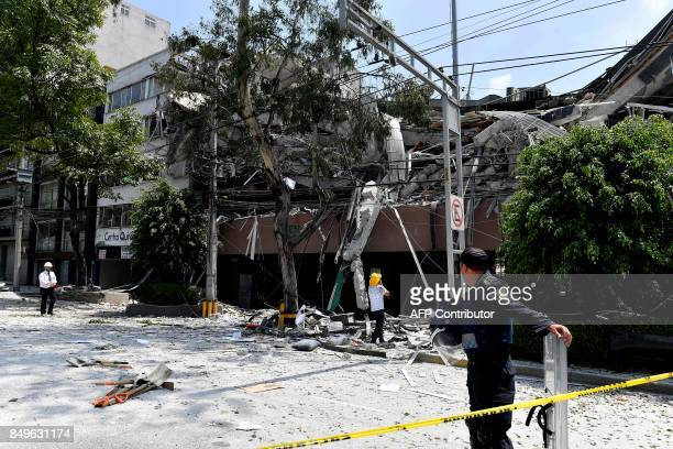 A police officer and other people look at a building which collapsed during a quake in Mexico City on September 19 2017 A powerful earthquake shook...