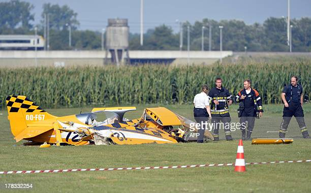 A police officer and rescue workers inspect the wreck of an ultralight aviation plane which crashed in CrasAvernas Hannut on August 29 in Belgium The...