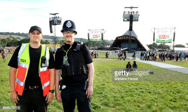 A police officer and security staff pose in front of The Pyramid stage during the Glastonbury Festival 2017 at Worthy Farm Pilton on June 22 2017 in...