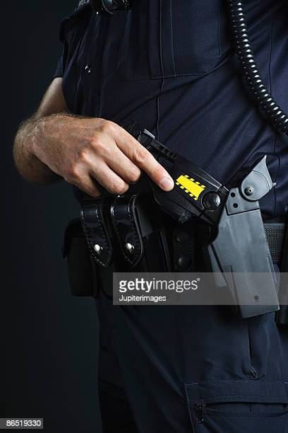 police officer and stun gun - police taser stock pictures, royalty-free photos & images
