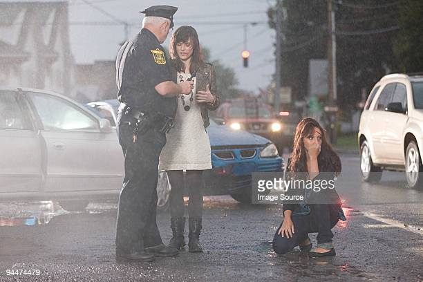 Police officer and young women at scene of accident