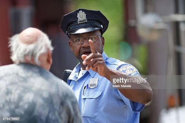 A police officer answers the questions of a concerned citizen near the wreckage of this week's Amtrak passenger train on May 15 2015 in Philadelphia...