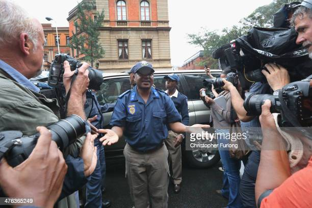 Police officer appeals to the media to keep back as they wait for Oscar Pistorius to arrive at North Gauteng High Court to face trial accused of the...
