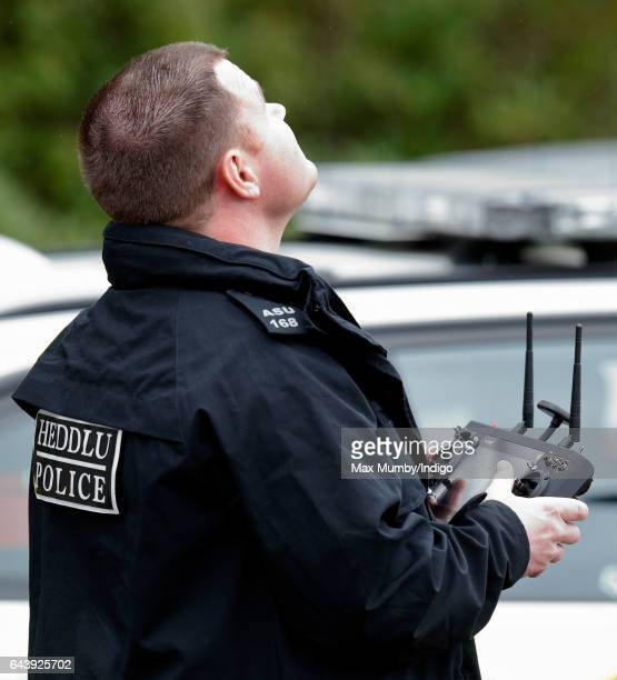 A Police Officer armed with a taser flies a camera equipped drone as Catherine Duchess of Cambridge arrives for a visit to MIST a child and...