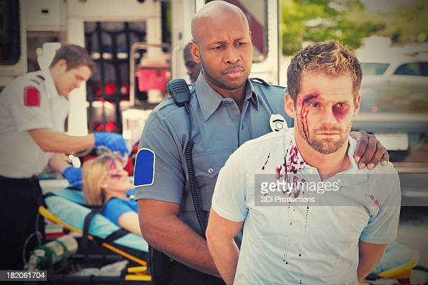 Police Officer Arresting Man in front of ambulance