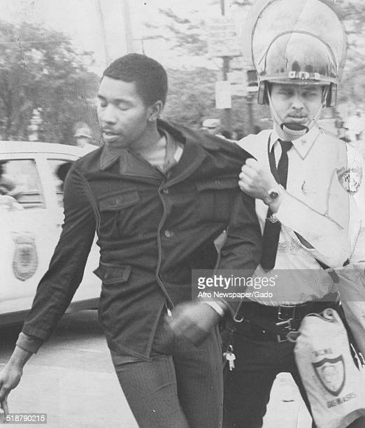 Police officer arresting protestors at Morgan State University during the aftermath of a civil rights demonstration Baltimore Maryland 1962