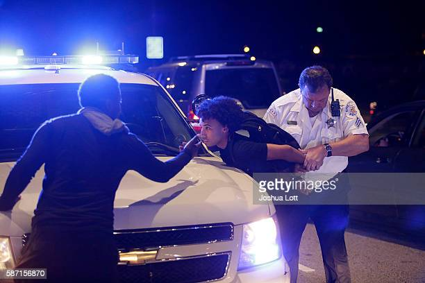A police officer arrests a demonstrator who was blocking motorist on Lake Shore Drive during a protest for the fatal police shooting of Paul O'Neal...