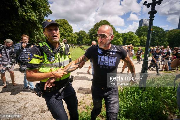 Police officer arrests a man taking part in a prohibited demonstration against the government's measures taken to stop the spread of the Covid-19...