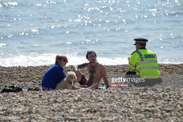 Police officer asks a couple to leave the beach on April 10, 2020 in Brighton, United Kingdom. The Coronavirus pandemic has spread to many countries...