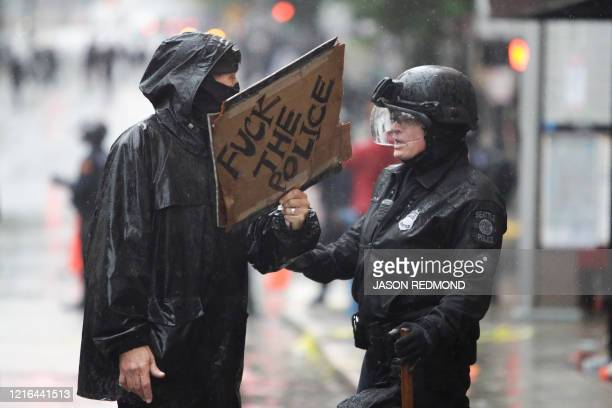 TOPSHOT A police officer asks a demonstrator to back up following protests against the death of George Floyd a black man who died May 25 in the...