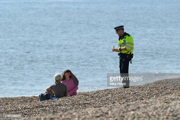 Police officer asks members of the public to leave the beach on April 10, 2020 in Brighton, United Kingdom. The Coronavirus pandemic has spread to...