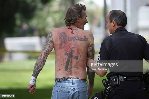 A police officer assists a reportedly homeless man who was attacked by antineoNazi demonstrators before the start of a rally by the National...