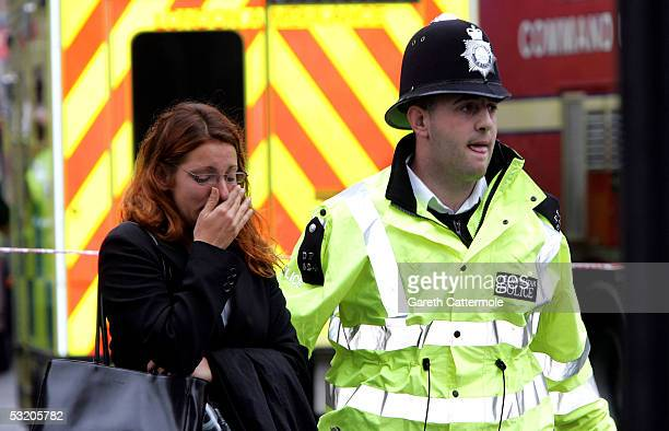 A police officer assists a woman at Edgware Road following an explosion which has ripped through London's inderground tube network on July 7 2005 in...