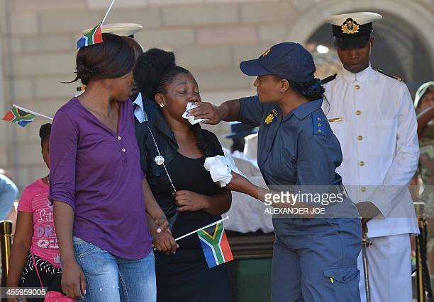 A police officer assists a woman crying after paying their respect to South African former president Nelson Mandela on the last day of Mandela's...