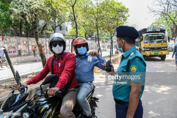 Police officer at a checkpoint seen talking with a man on a motorcycle. Police checkpoints are set up in various places in the capital to stop the...