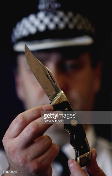 A Police officer at St Leonards Police Station displays a knive at the launch of a national knife amnesty May 23 2006 in Edinburgh Scotland From...