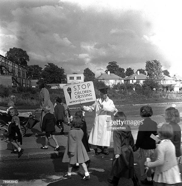 1953 A police officer at the school crossing patrol in Northolt London watches as children cross the road