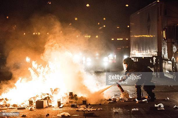 A police officer attempts to extinguish a fire on the I85 during protests in the early hours of September 21 2016 in Charlotte North Carolina The...