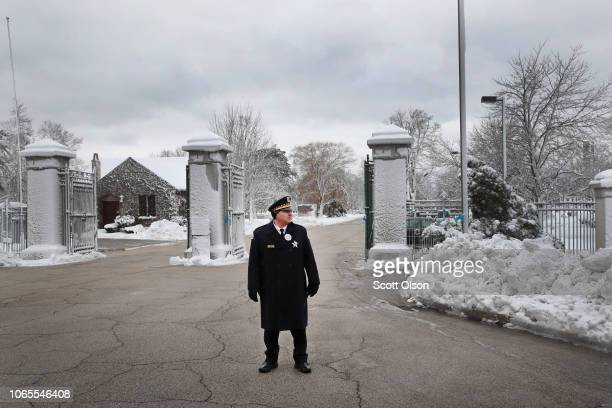 A police officer awaits the funeral procession carrying the remains of Chicago Police Officer Samuel Jimenez at the gate of Ridgewood Memorial Park...